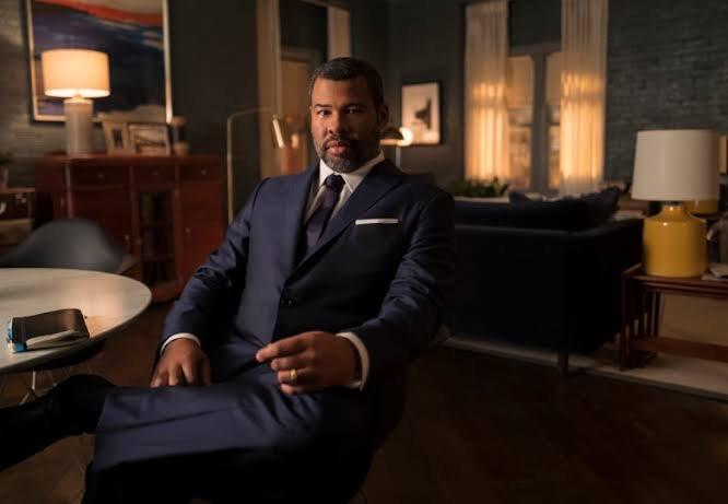 Jordan Peele sentado en una silla mirando directamente a la cámara.